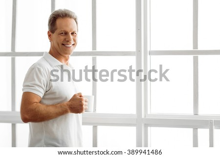Handsome middle aged man is holding a cup, looking at camera and smiling while standing near the window at home - stock photo