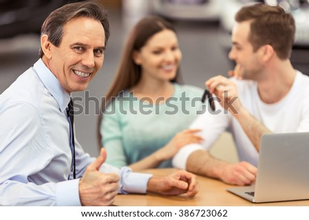 Handsome middle aged man is showing Ok sign and smiling, young couple is using laptop and holding keys while sitting in motor show