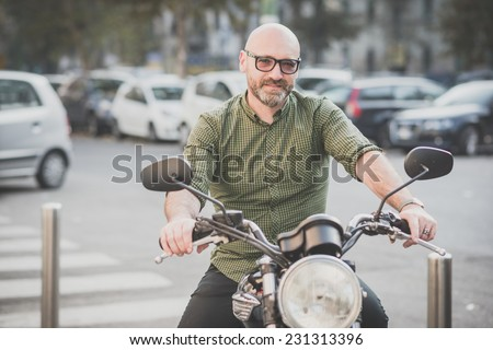 handsome middle aged man motorcyclist in the city - stock photo