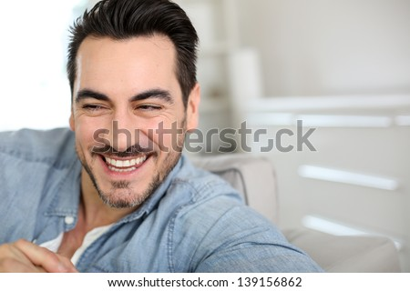 Handsome middle-aged man relaxing in sofa - stock photo