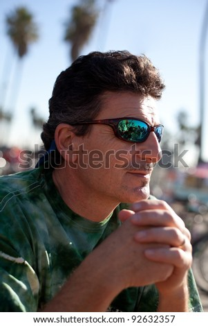 Handsome Middle aged Man sitting at the beach with a reflection of his son in his Sunglasses