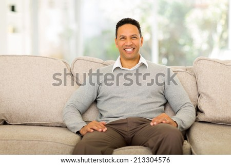 handsome middle aged man sitting on the couch at home - stock photo