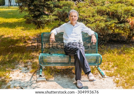 Handsome middle-aged man with salt pepper hair dressed with white shirt, blue slacks and beige moccasins is resting on a bench in city park keeping his arms opened: he shows a reassuring look