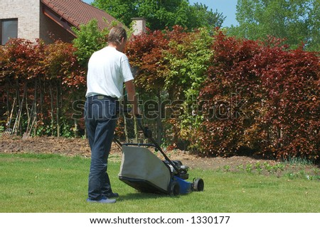 Handsome Middle aged man working in the garden with lawnmower,