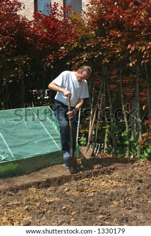 Handsome Middle aged man working in the garden, working with spade.