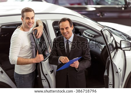 Handsome middle aged salesman is presenting a car to handsome young customer in a motor show. Both looking at camera and smiling