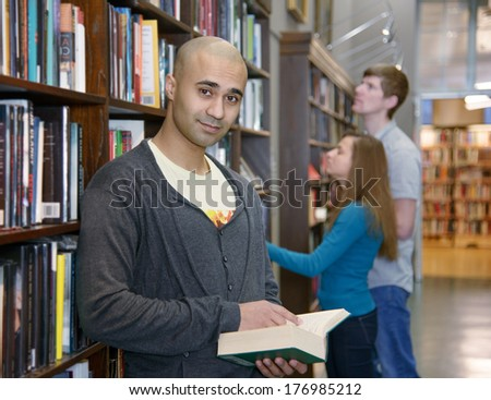 Handsome middle eastern student boy standing by a bookshelf in a library, two european students choosing books no background.