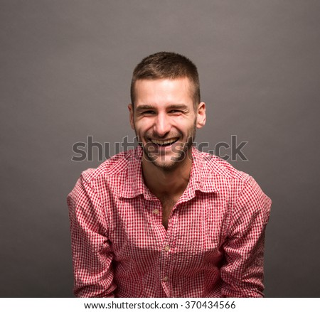 Handsome model man happy smiling in studio. Short-haired man in pink shirt toothy laughing over grey background.