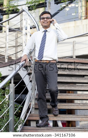 Handsome  modern businessman  walking in town and calling on mobile phone