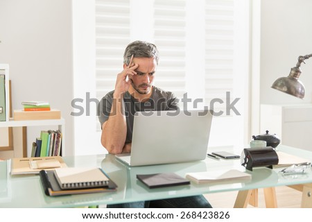 handsome modern man wearing a tee-shirt, working on his laptop sitting at his desk, his office is contemporary et luminous - stock photo