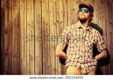 Handsome modern young man standing near a wooden fence. Fashion.  - stock photo