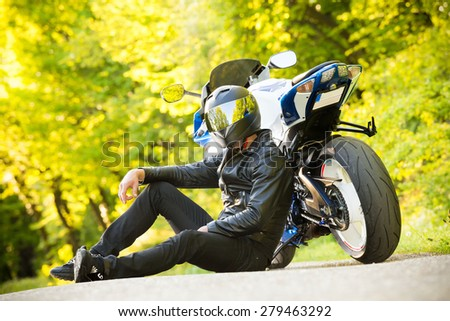 Handsome motorcyclist in black posing in front of his super sport motorcycle. Soft focus. Lens flare - stock photo
