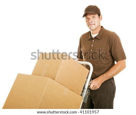 Handsome moving man moves a stack of boxes on his dolly.  Isolated on white. - stock photo
