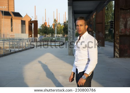 Handsome muscular blond man standing in city setting looking at camera, large copyspace - stock photo