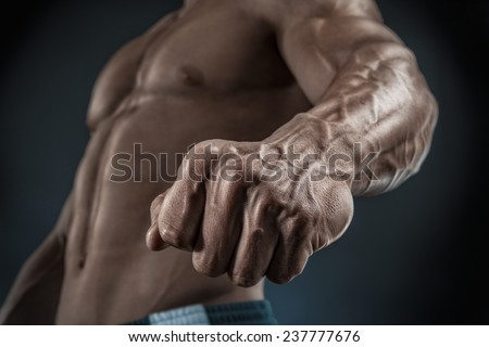 Handsome muscular bodybuilder demonstrates his fist and vein, blood vessels. Studio shot on black background. - stock photo
