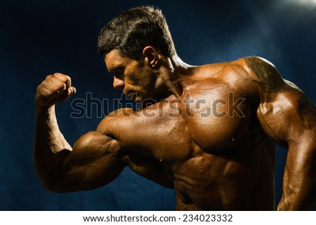 Handsome muscular bodybuilder demonstrates his muscles. Beauty of the male body in shades of yellow - stock photo