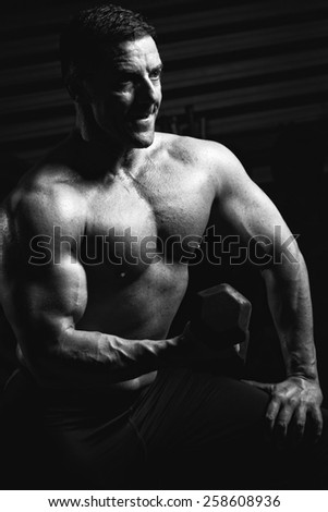 Handsome muscular bodybuilder.Muscular young man lifting weights on dark background