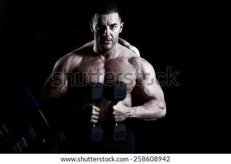 Handsome muscular bodybuilder.Muscular young man lifting weights on dark background - stock photo