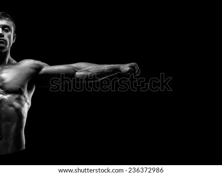 Handsome muscular bodybuilder posing and keeping arms outstretched. Muscular and fit young bodybuilder posing raising his hands on black background. Abstraction Black and white photo
