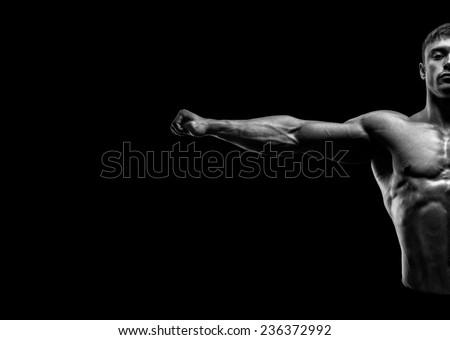Handsome muscular bodybuilder posing and keeping arms outstretched. Muscular and fit young bodybuilder posing raising his hands on black background. Abstraction Black and white photo - stock photo