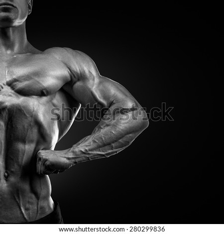 Handsome muscular bodybuilder posing on Front Lat Spread. Display lat width, chest thickness, shoulder width, front arm and forearm size, quadriceps mass and separation,  calf development.