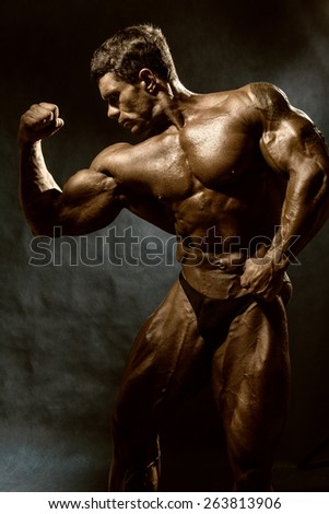 Handsome muscular bodybuilder posing over dark background. Trained athlete's body. toned image - stock photo