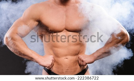 Handsome muscular bodybuilder posing over smoke background - stock photo