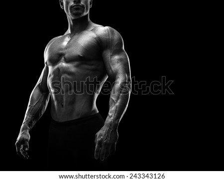 Handsome muscular bodybuilder preparing for fitness training. Black and white photo with copy space - stock photo