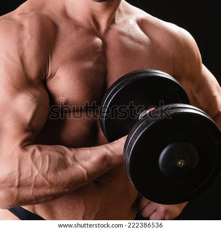 Handsome muscular bodybuilder with dumbbell posing over black background - stock photo