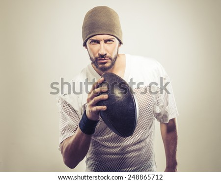 Handsome muscular football player holding ball and posing - stock photo