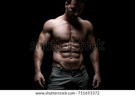 Handsome muscular guy posing, isolated on black background
