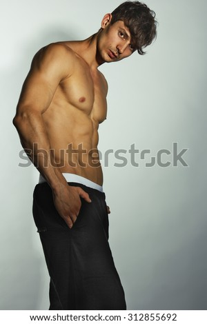 Handsome muscular male model in trendy black pants and white underwear posing over grey background. Studio shot - stock photo