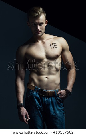 """Handsome muscular male model with intense glance posing over grey background. Perfect body with the inscription """"he"""" on his chest . Studio shot - stock photo"""