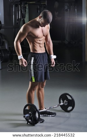 Handsome Muscular Male Model With Perfect Body Posing Behind Weight  - stock photo