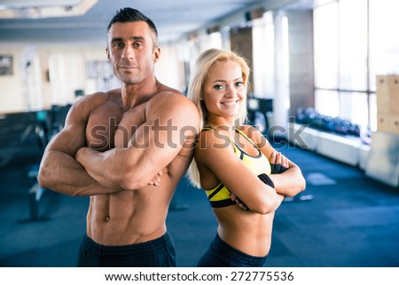 Handsome muscular man and beautiful sporty woman with arms folded standing in gym. Looking at camera - stock photo