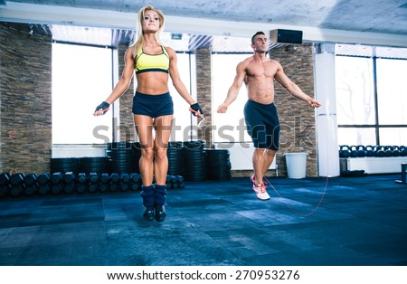 Handsome muscular man and beautiful sporty woman workout with jumping rope in crossfit gym - stock photo
