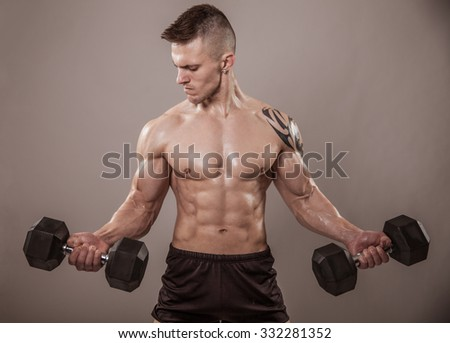 Handsome muscular man exercise with weights.