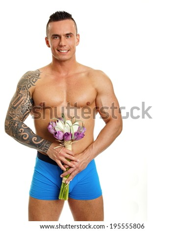 Handsome muscular man hold bouquet of tulips, right you can write some text - stock photo