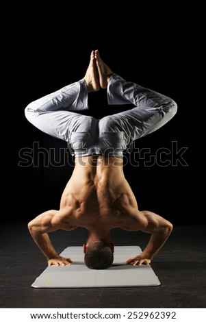 Handsome muscular man is doing yoga on black background - stock photo
