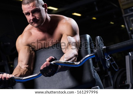 Handsome muscular man is working out in a gym - stock photo