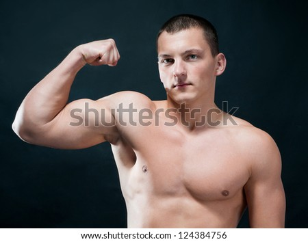 Handsome muscular man isolated on black - stock photo