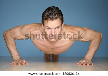 Handsome muscular man looks at camera while performing pushup on floor with blue wall background