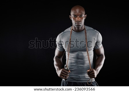 Handsome muscular man posing with jumping rope on black background. African fitness model with skipping rope. - stock photo