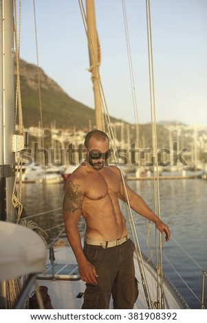 Handsome muscular man sailing at Mediterranean sea, traveling the world by sailboat, male model