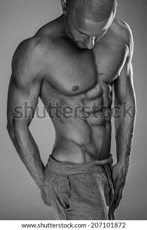Handsome muscular man shirtless wearing grey pants - stock photo