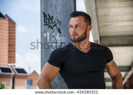 Handsome muscular man standing outdoor in city - stock photo