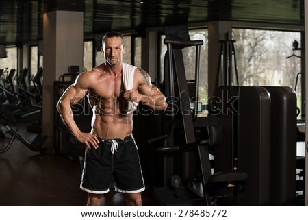 Handsome Muscular Man With A Towel On His Shoulders In Modern Fitness Center - stock photo
