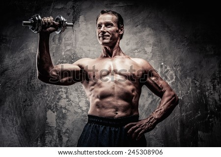 Handsome muscular man with dumbbell - stock photo