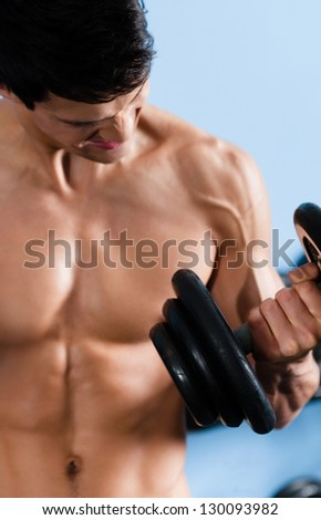 Handsome muscular man with naked body uses his dumbbell to exercise flexing bicep muscle - stock photo