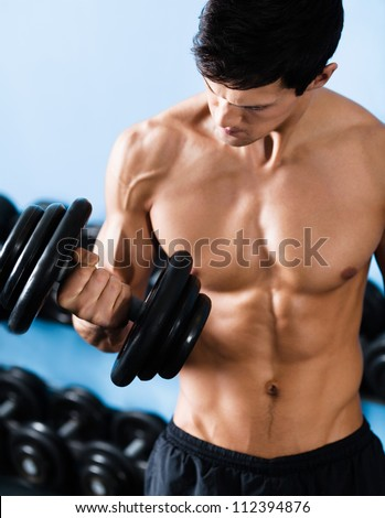 Handsome muscular man with nude body uses his dumbbell to exercise flexing bicep muscle
